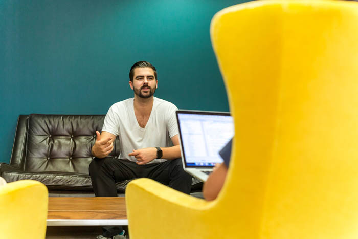 man explaining to yellow armchair