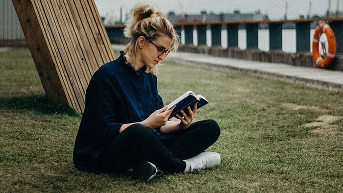 girl sitting on grass reading