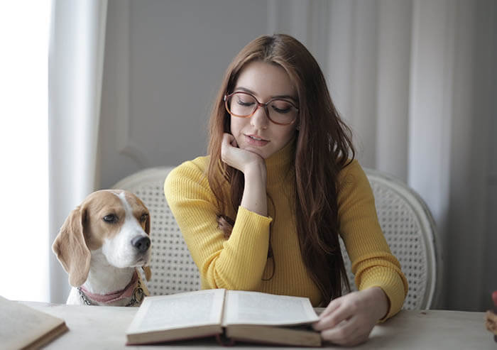 girl and dog reading a book