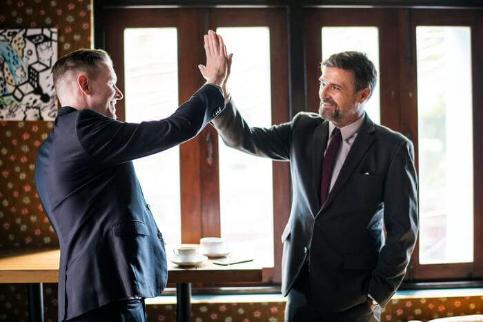two men wearing suits highfive