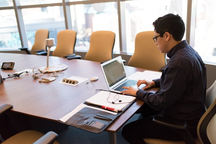man sitting at a conference table with laptop alone
